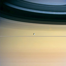 One of Saturn's moons appears to hover above the planet's rings.